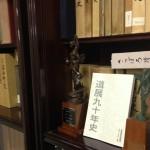 記念誌・町史を収めた本棚とともに
